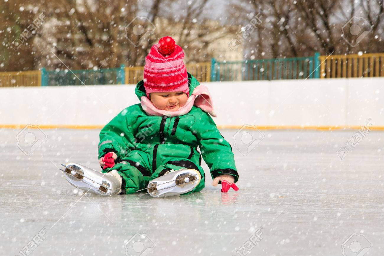 cute little girl sitting on ice with skates after the fall - 45613871