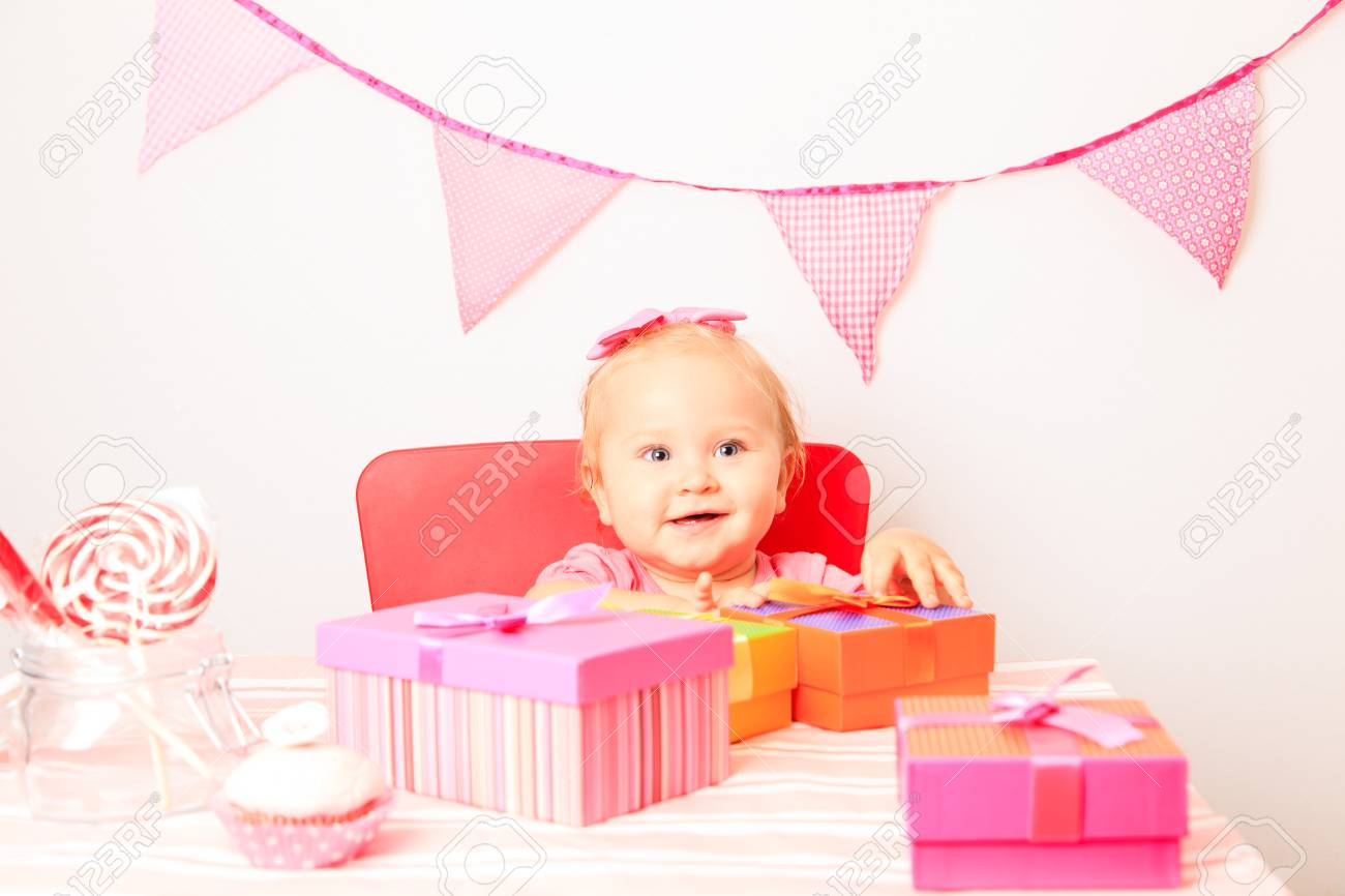 5c20c8f7c7ddd little girl taking presents at first birthday party Stock Photo - 48284512