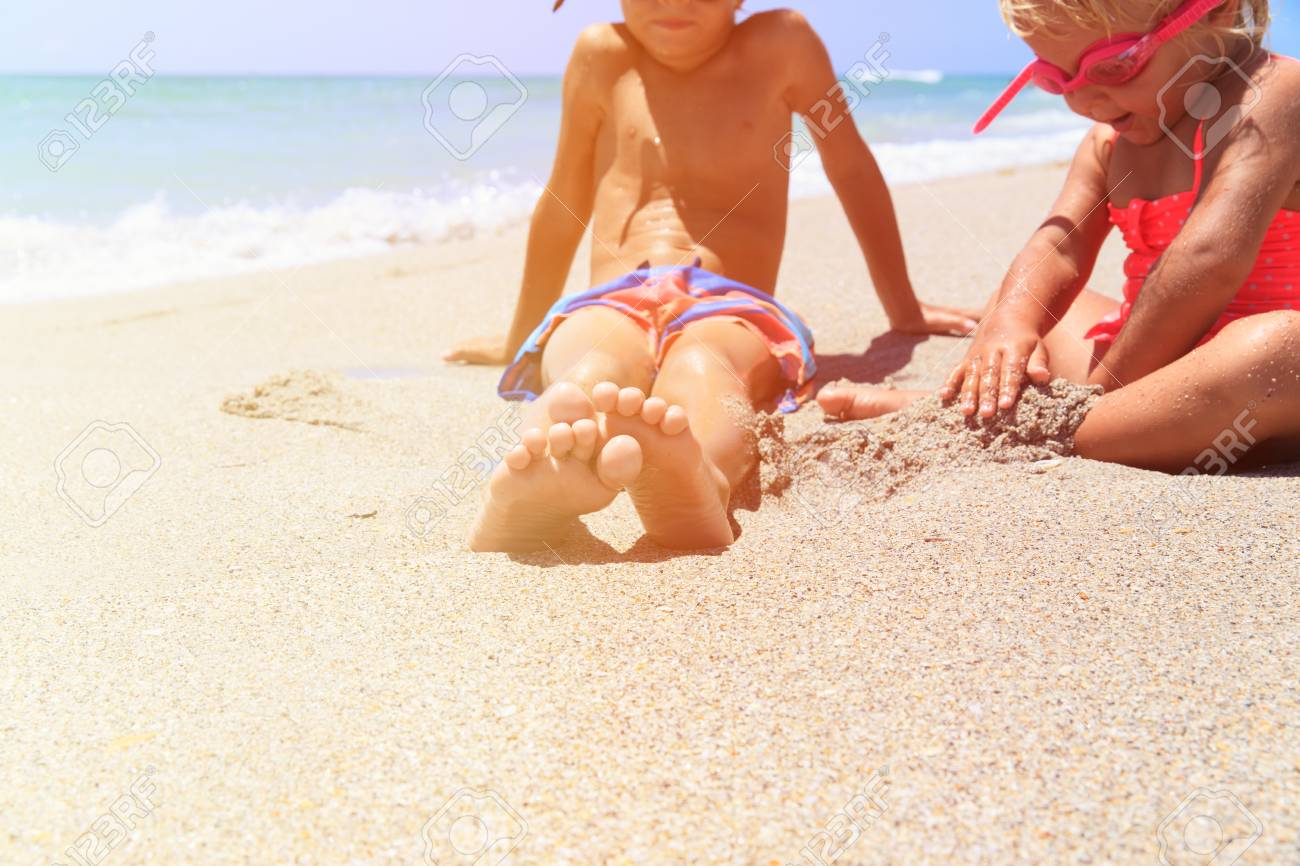 cute little boy and girl play with water on tropical beach - 59951911