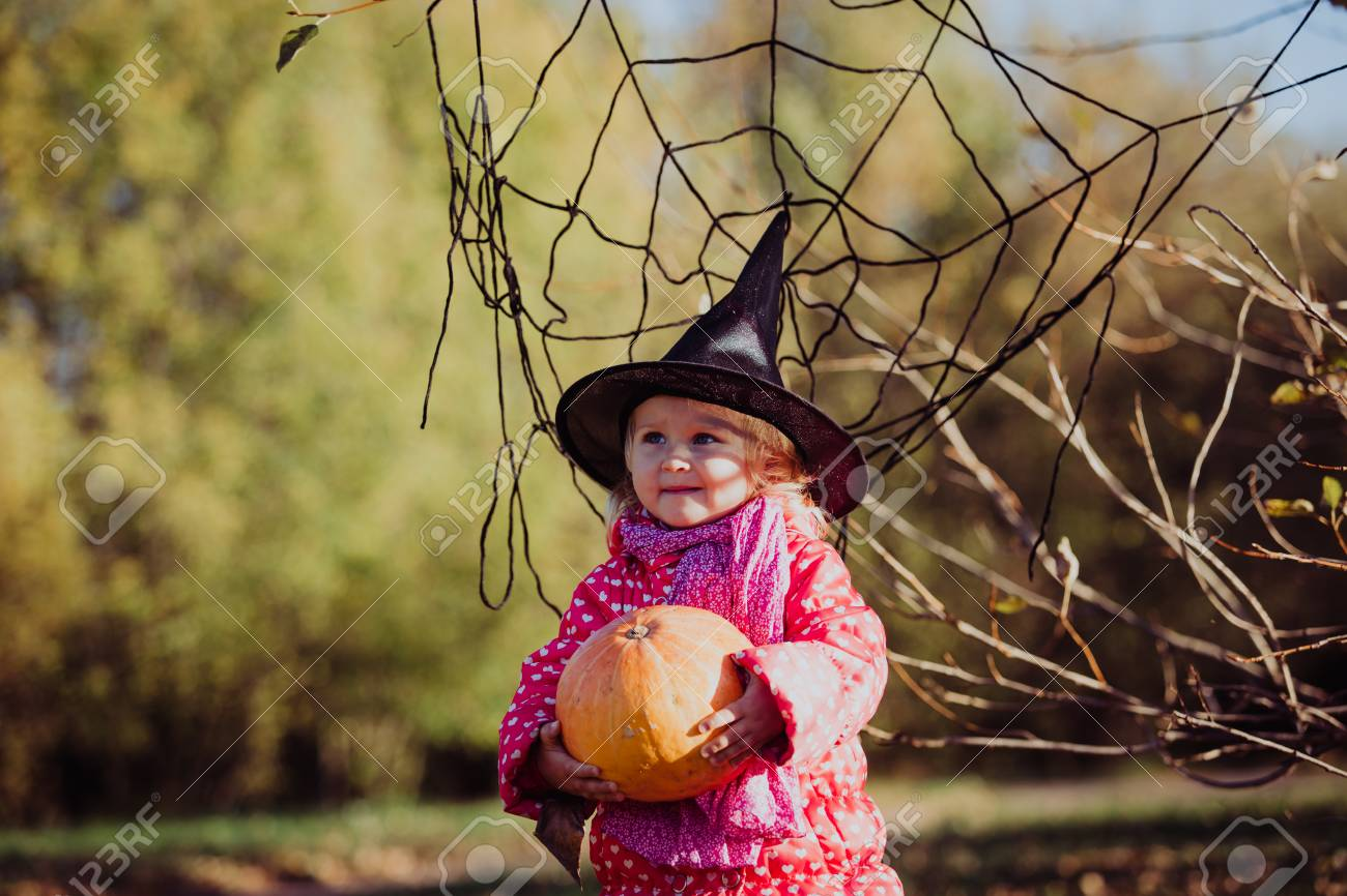 little girl in halloween costume in autumn park kids trick or treating stock photo