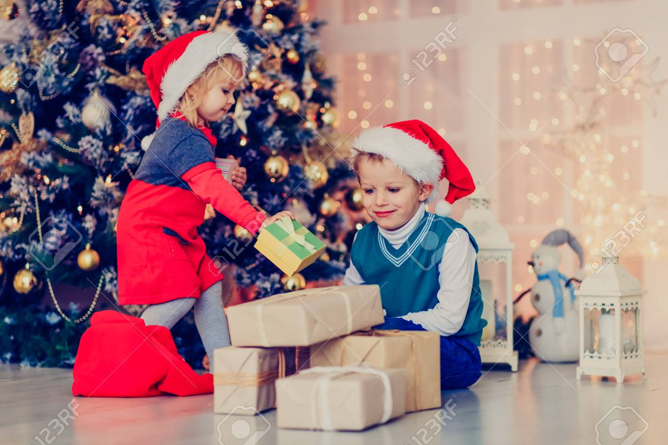 Kids Opening Christmas Presents In Decorated Living Room, Christmas ...