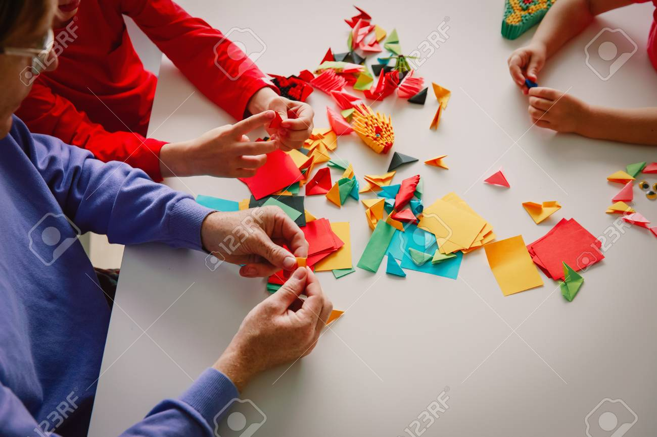 Teacher And Kids Making Origami Crafts With Paper Stock Photo