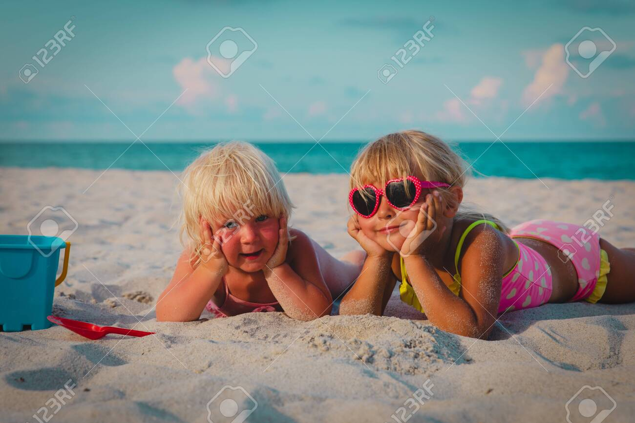 cute happy little girls play with sand on beach - 123919270