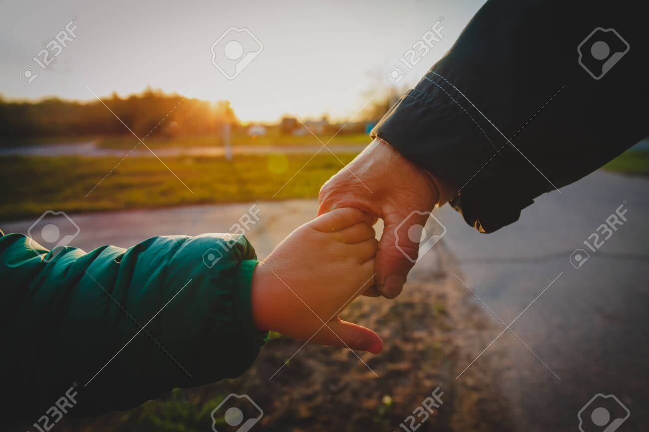grandmother holding grandchild hand in nature, parenting concept - 123938314