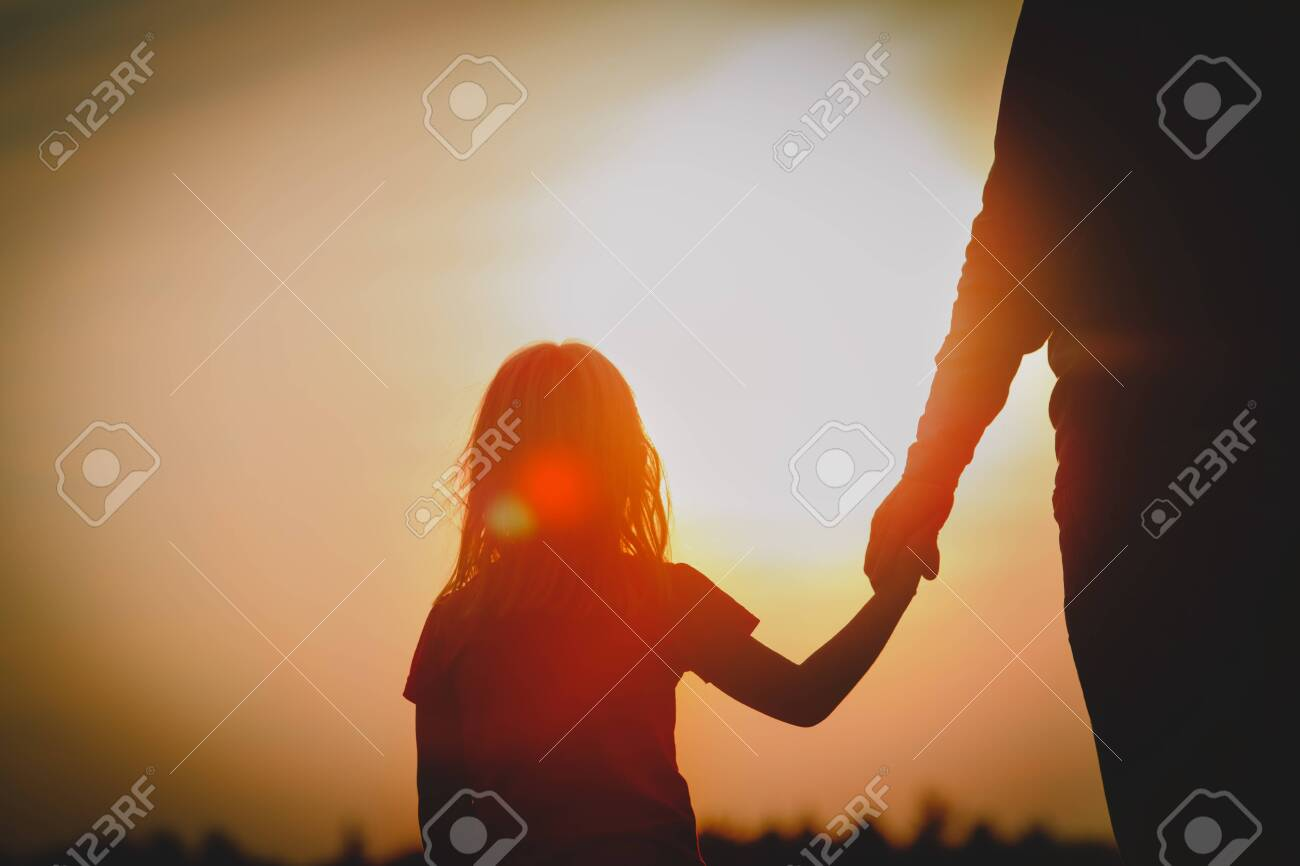 silhouette of little girl holding parent hand at sunset - 123919921