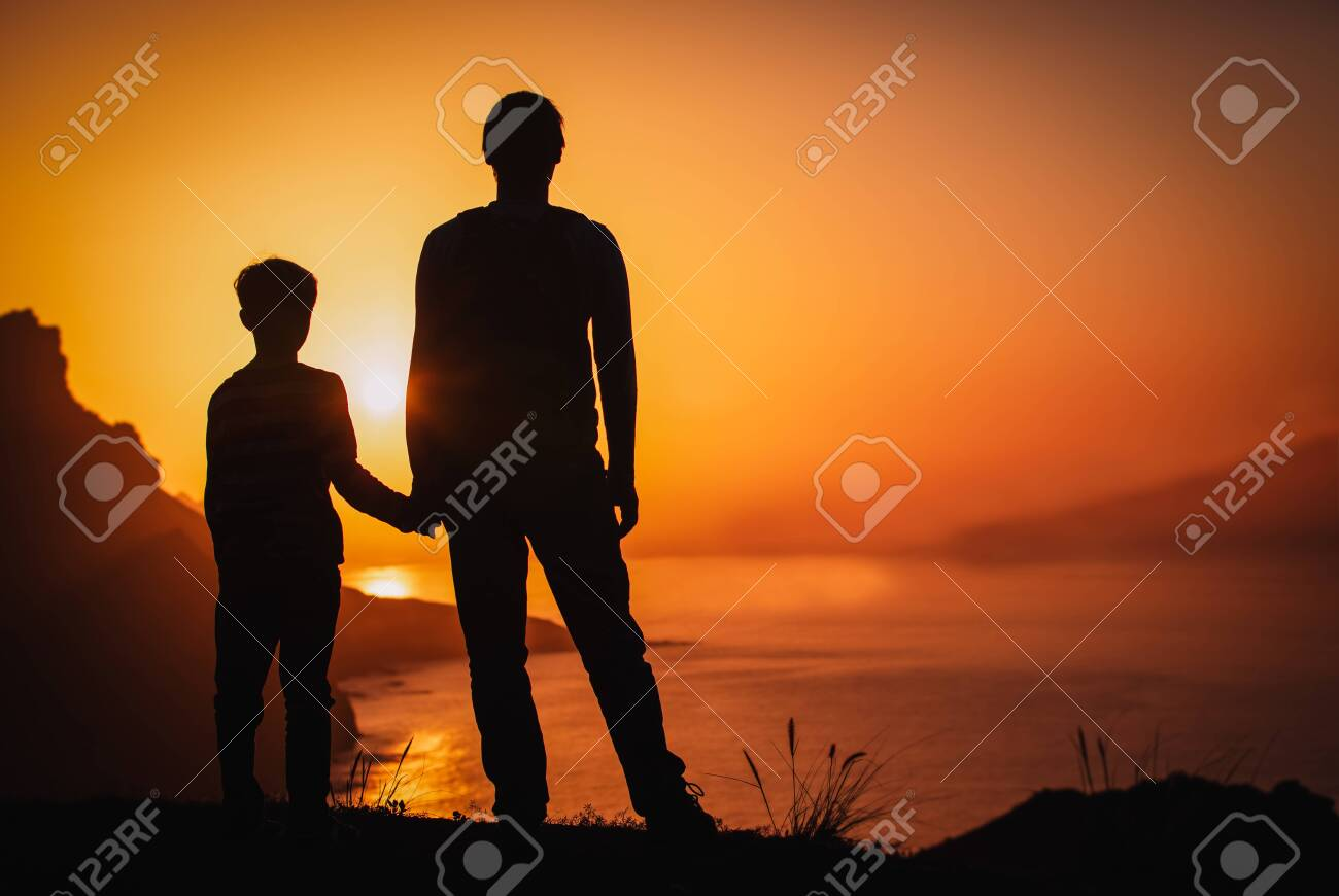 silhouette of father and son holding hands in sunset nature - 125871306