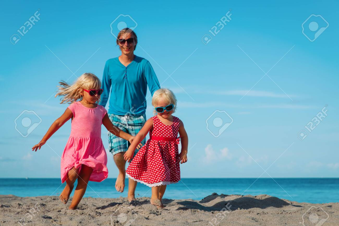 happy family -father with cute little daughters play at beach - 126434348