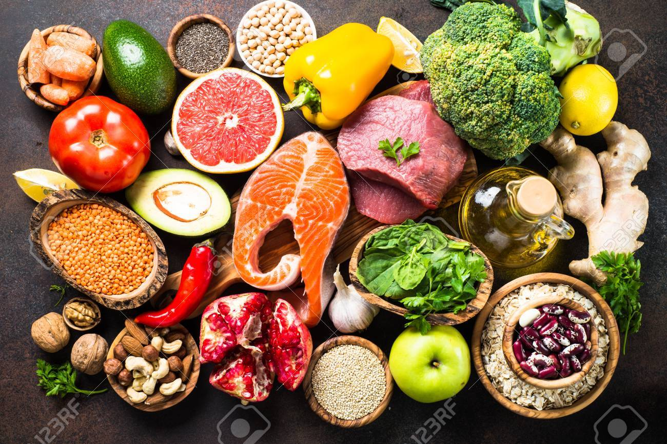 Balanced diet food background. Organic food for healthy nutrition, superfoods. Meat, fish, legumes, nuts, seeds, greens, oil and vegetables. Top view on dark stone table. - 88714208