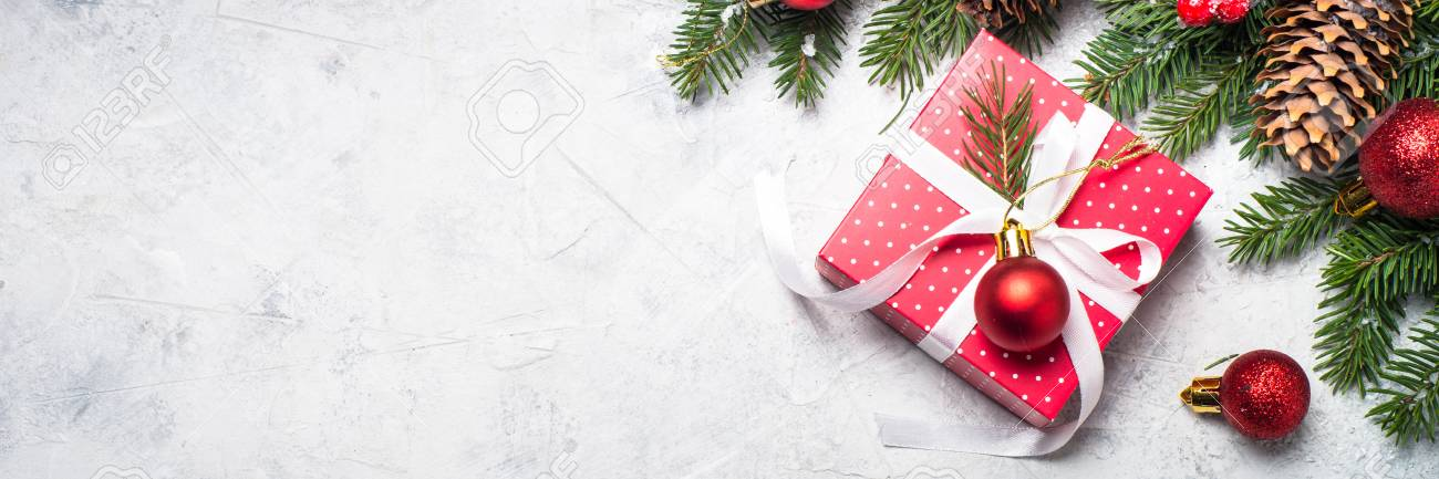 christmas background red christmas present box fir tree branch and decorations on gray stone