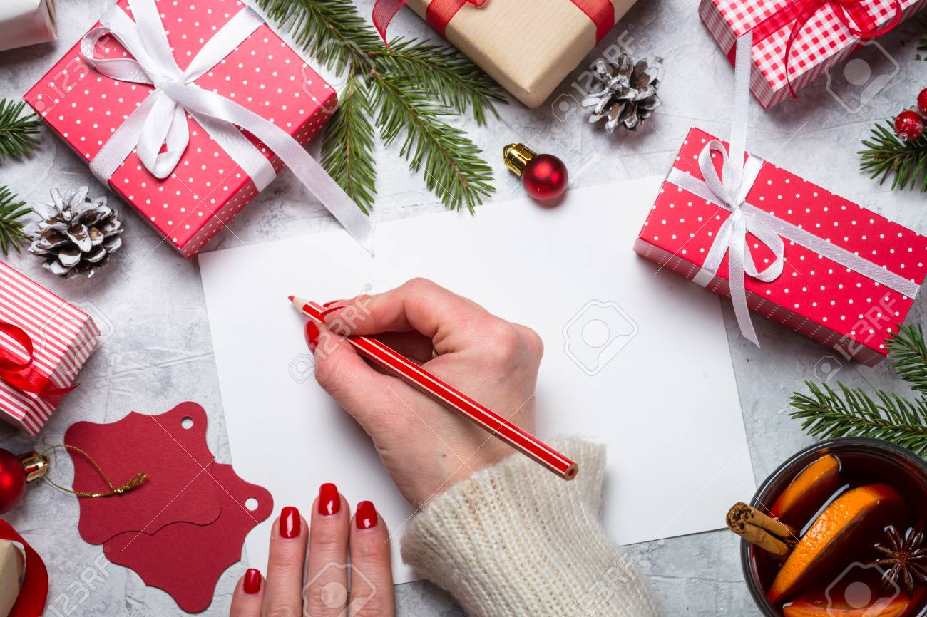 Christmas background. Woman packing Christmas present box and write wishes. Top view. - 90026374