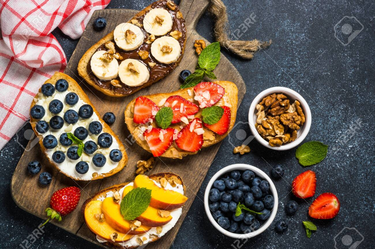 Sweet toast assortment. Chocolate banana, cream cheese and peach, peanut butter and strawberry, cream cheese and blueberry toasts. Black stone background, top view. - 128116150