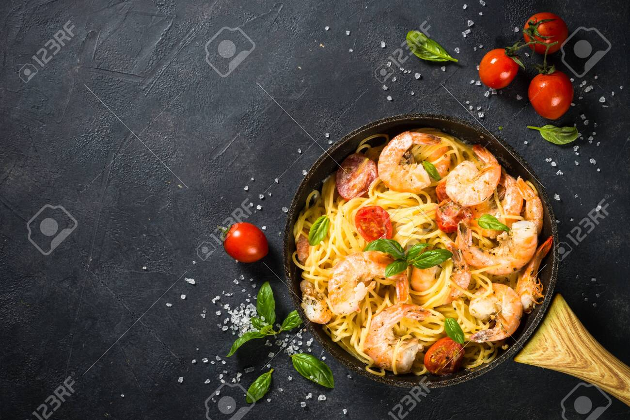 Pasta seafood. Pasta Spaghetti with shrimp, cream sauce and basil. Top view on black stone table. - 144540260