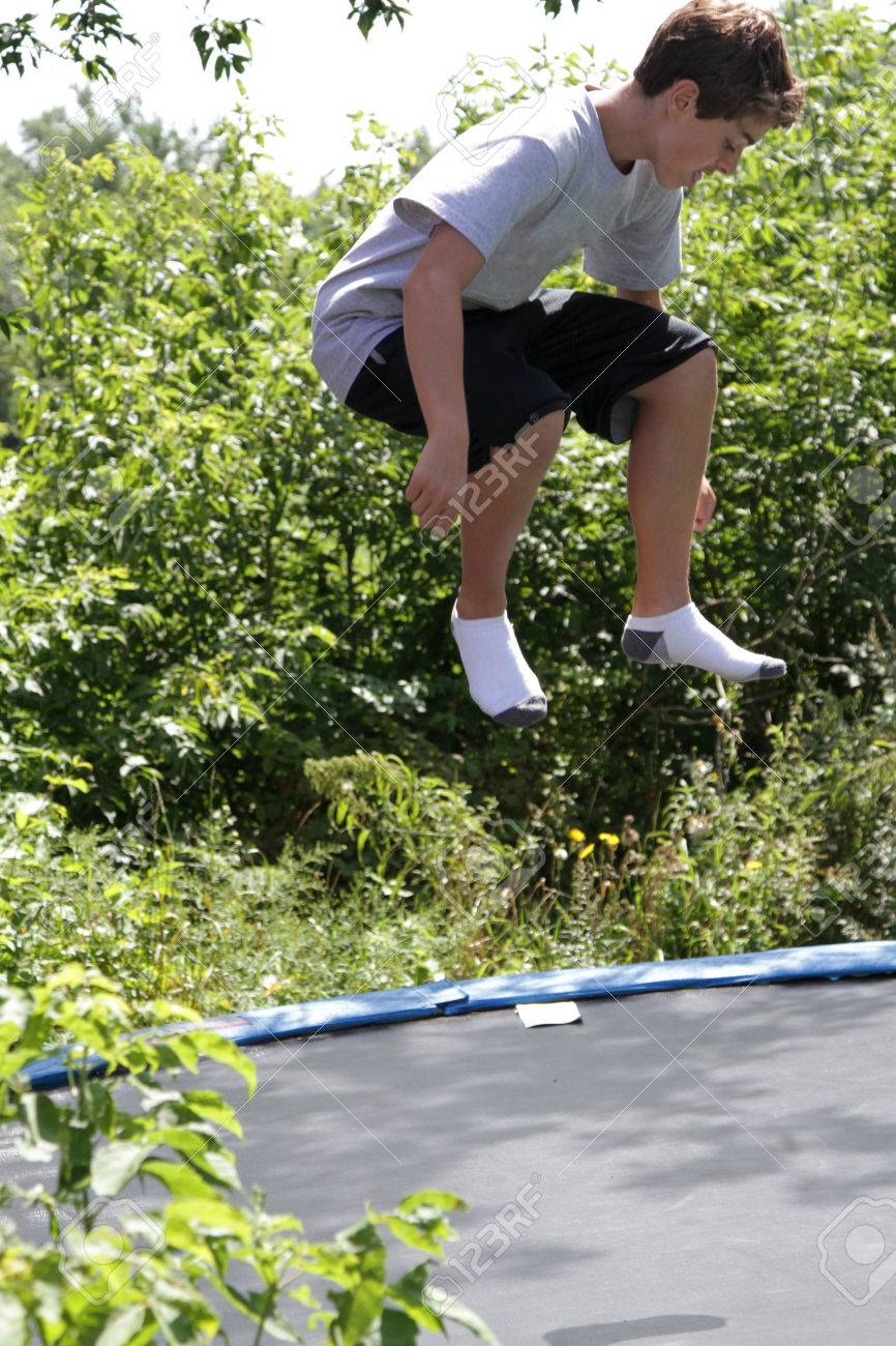 Stock Photo - Teen boy bouncing on a trampoline