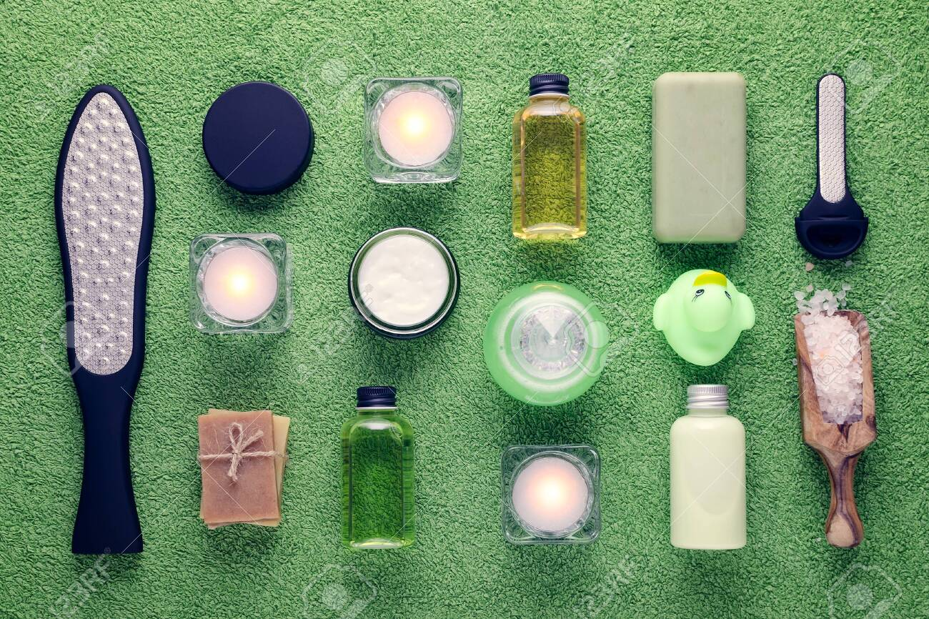 wellness and spa products, laser feet grater, cream, lotion, soap, pink salt and candle on green towel - 140258395
