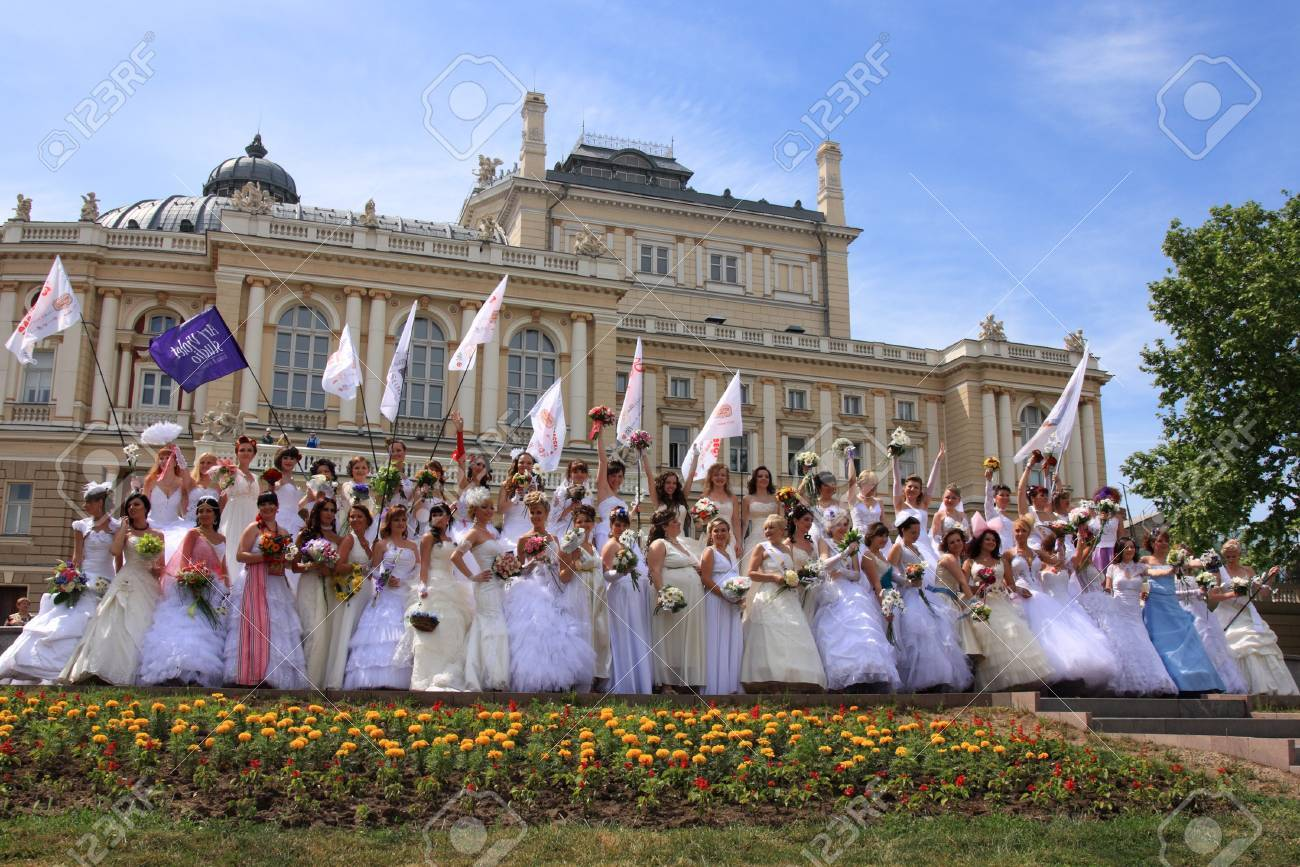 "ODESSA,UKRAINE – MAY 29: Annual event "" Bride Parade"". Happy excited participants in fiancee's gowns take part in celebration of marriage and romance Bride Parade on May 29 , 2011 in Odessa,Ukraine  Stock Photo - 9638281"