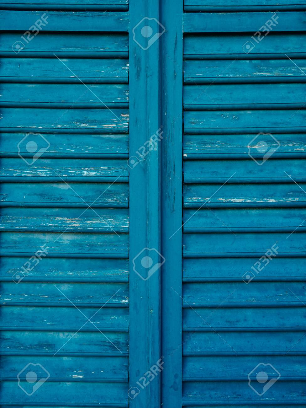 Stock Photo - Wooden window shutters in blue. Antique homemade shutters on the windows.