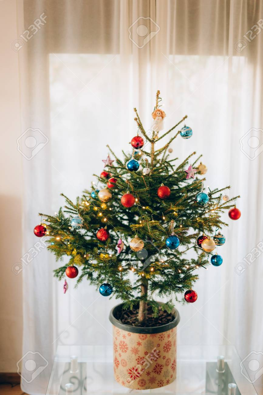 A Small Christmas Tree In A Pot Decorated With Balls Garlands Stock Photo Picture And Royalty Free Image Image 85874777