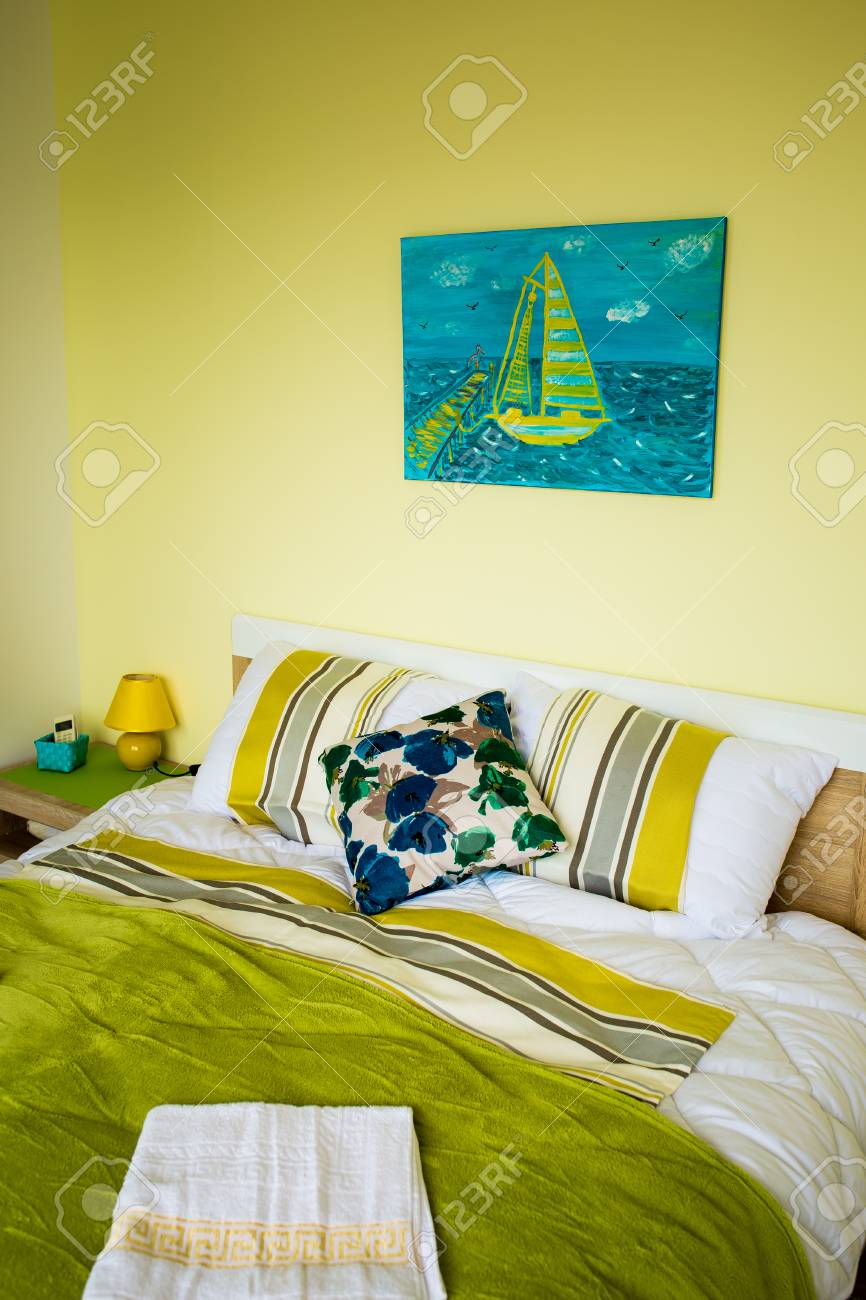 Interno della camera da letto in colori verdi. Un grande letto matrimoniale  è verde.
