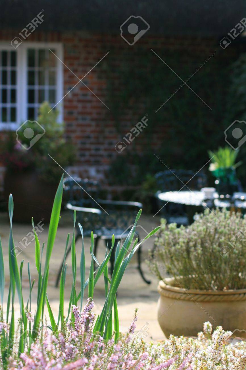 wrought iron garden furniture. A Rural Garden Patio Scene With Wrought Iron Furniture To The Background Set Against