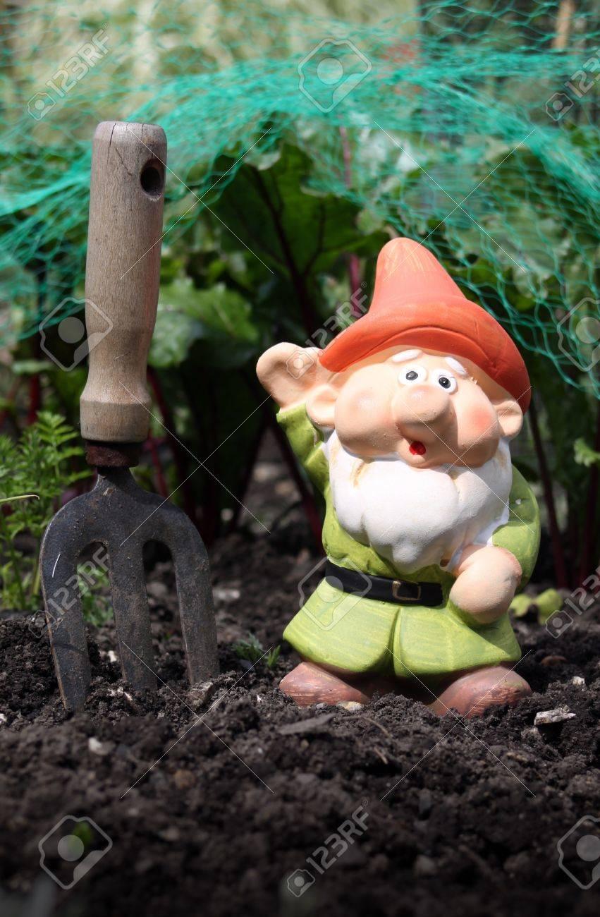 Une petite décoré colorés barbu nain de jardin avec un chapeau orange et  vert tunique, défini dans un potager avec une main petit jardin fourche ...