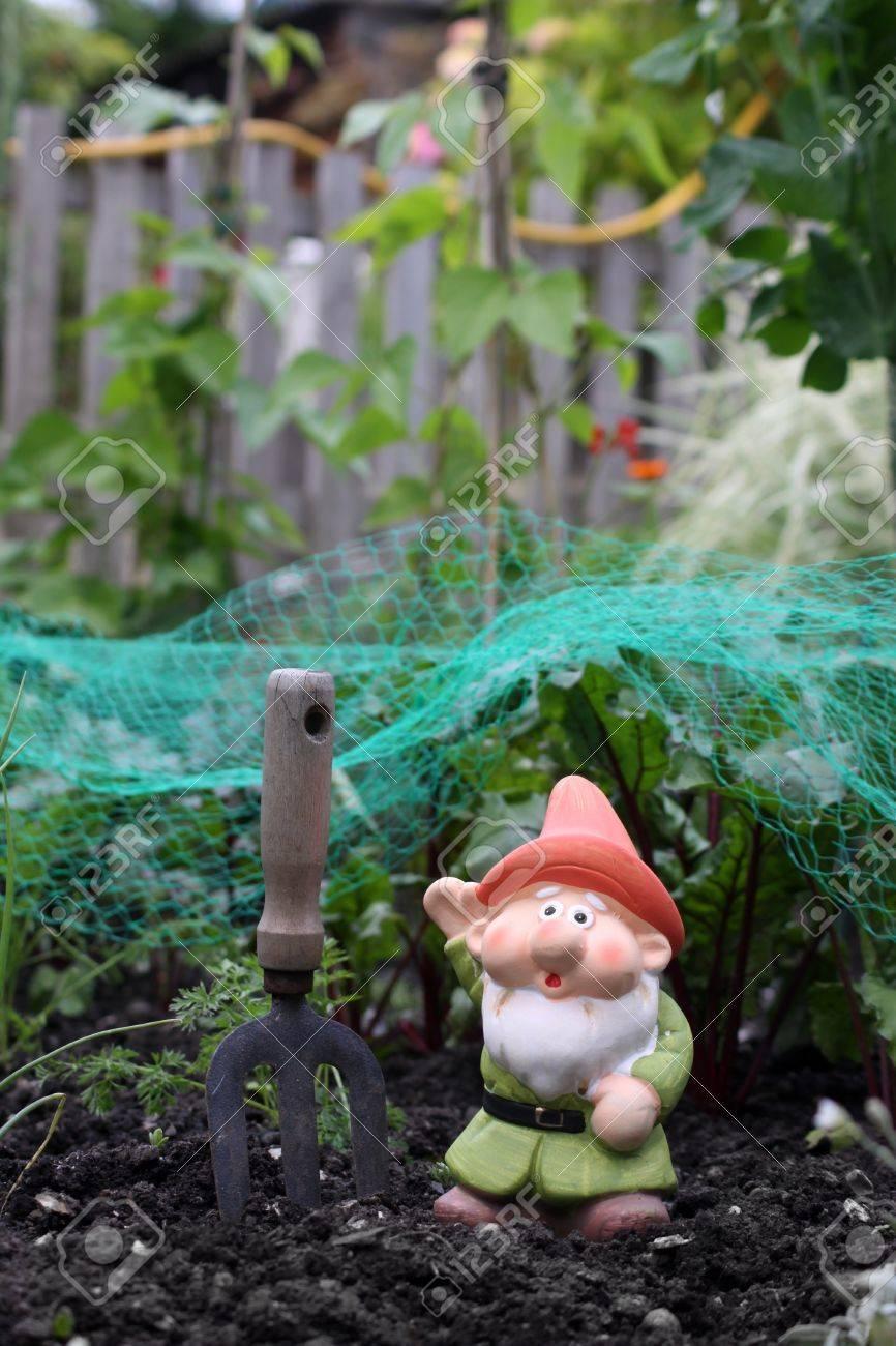 Une petite décoré colorés barbu nain de jardin avec un chapeau orange et  vert tunique, définie dans une parcelle de jardin et légumes urbain ville.  Un ...