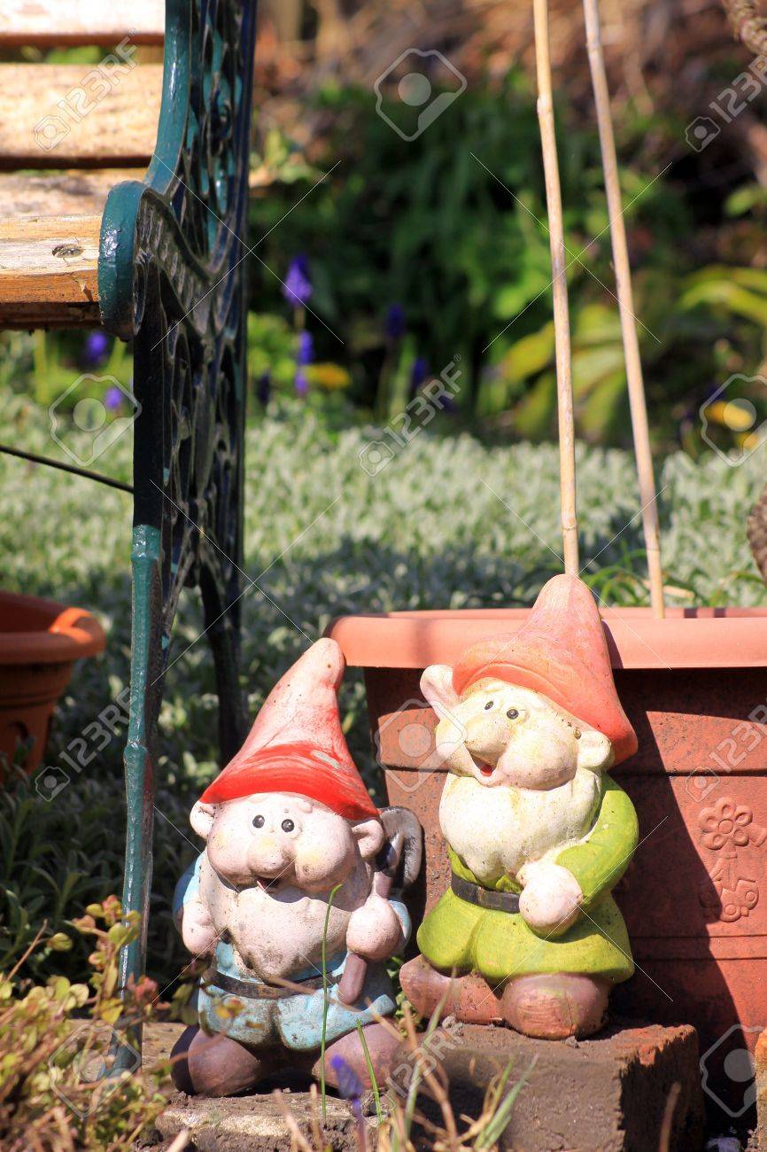 Deux nains de jardin dans un jardin de ville à côté d\'une fer forgé vert et  banc de jardin en bois et en face d\'une couleur de plantes en pot ...