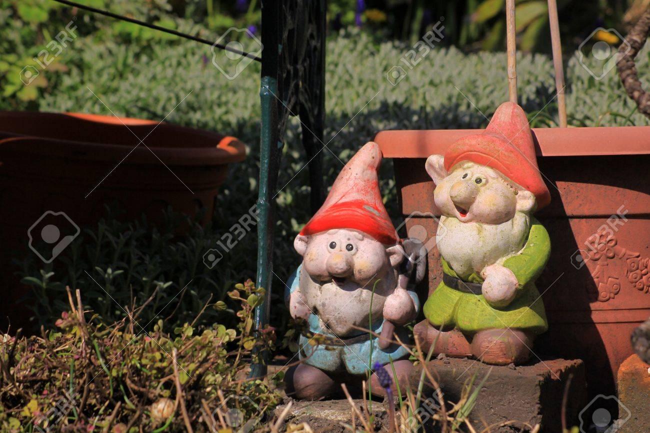 Deux nains de jardin dans un jardin de ville à côté d\'une table de jardin  et en face d\'une couleur de plantes en pot plastique terre cuite. Situé sur  ...
