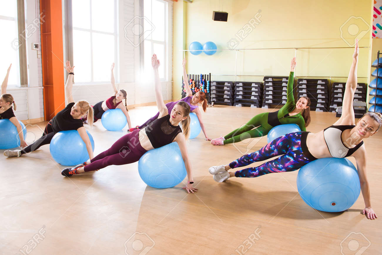 A group of young women go in for sports on fitness balls. - 165889353