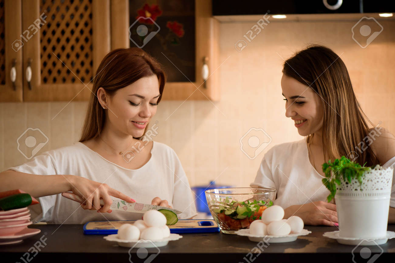 Young girlfriends chopping vegetables with twin in a family home kitchen. - 166330296