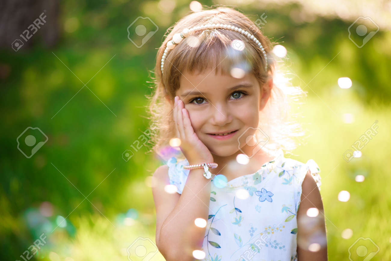 Sweet, happy, smiling five year old girl laying on a grass - 166727311