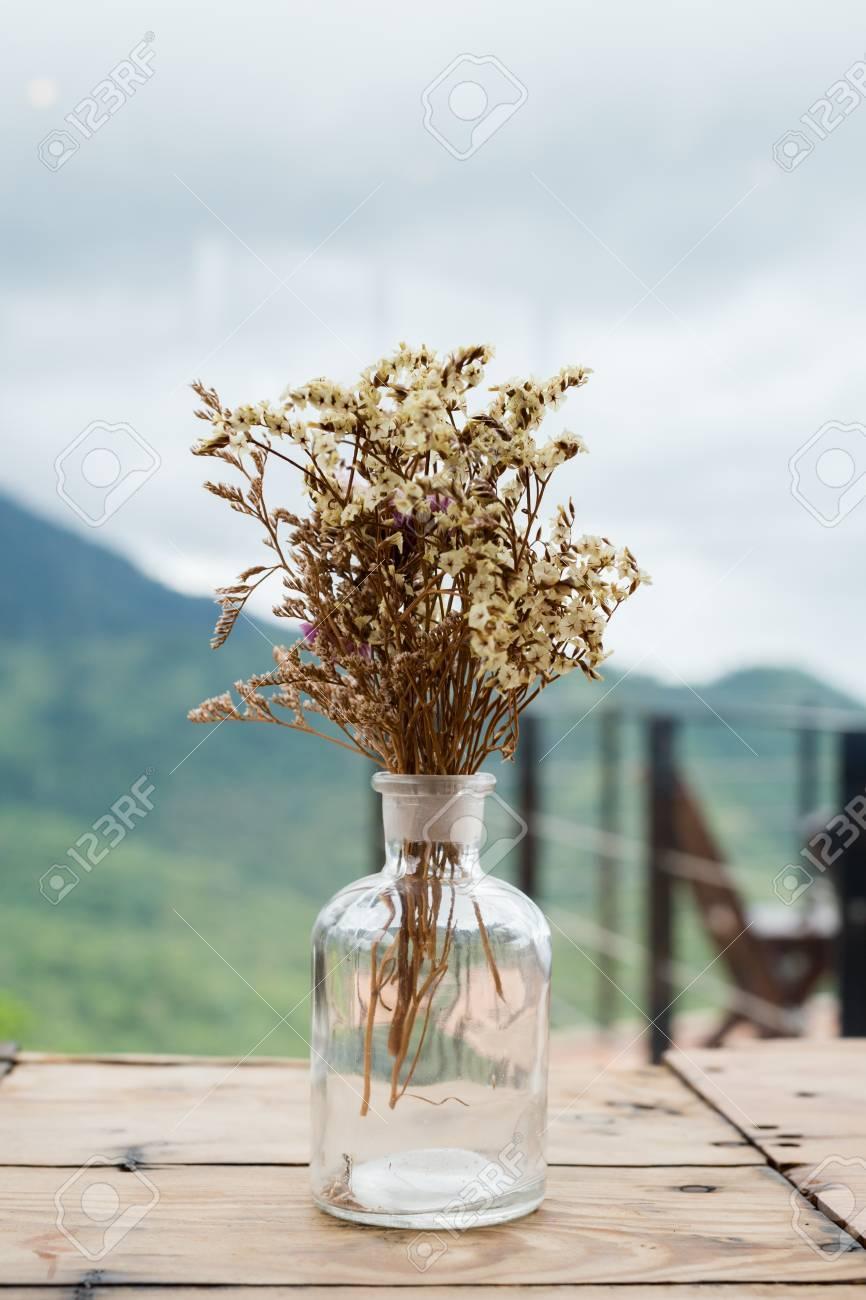 Banque d\u0027images , Bouquet de fleurs séchées dans un vase de verre sur la  table en bois.