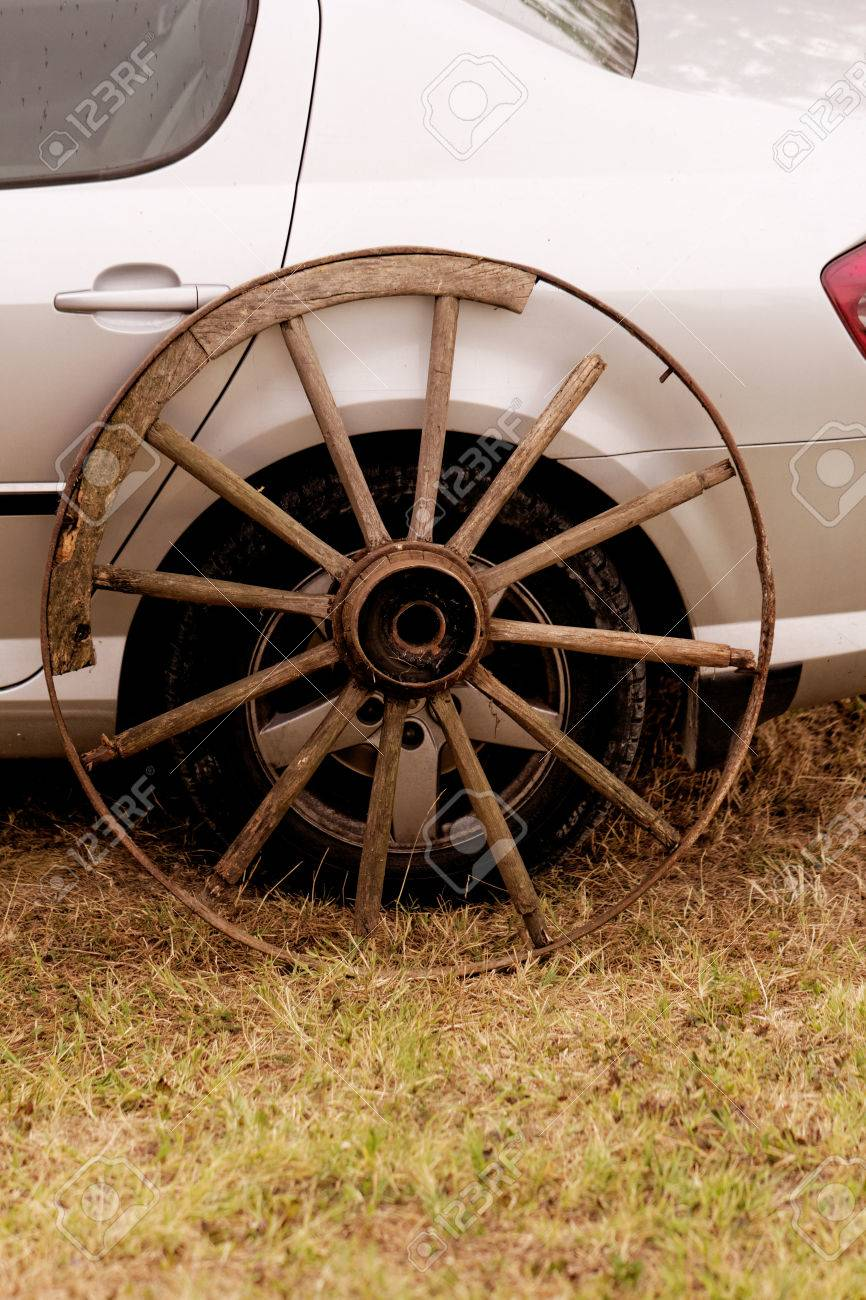old broken wagon wheel side by new cars back Stock Photo - 22881715