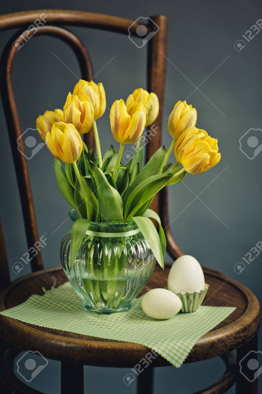 Beautiful bright yellow tulips in still life in glass vase on beautiful bright yellow tulips in still life in glass vase on antique wooden chair with fresh reviewsmspy