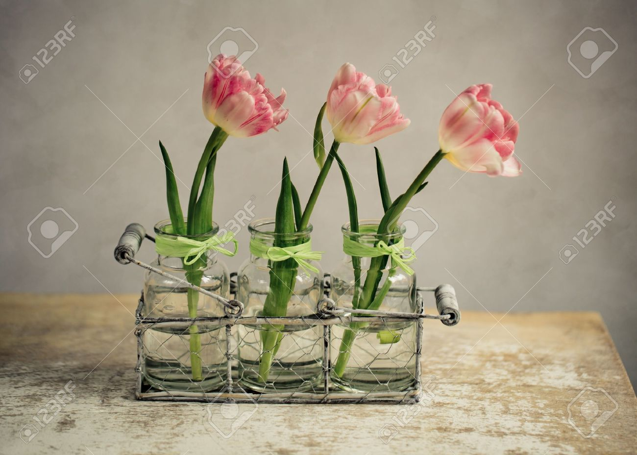 stock photo three beautiful pastel colored pink tulips in glass vases and decorative metal basket - Decorative Glass Vases