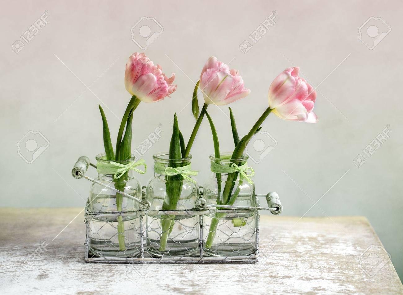 tres hermosos tulipanes de color rosa color pastel en jarrones de cristal y una cesta de