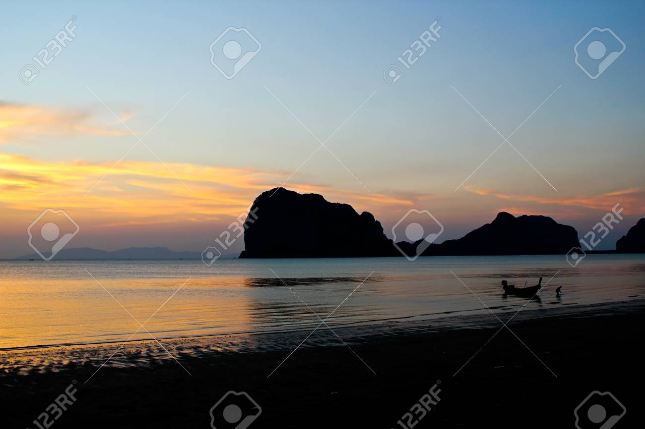 Silhouette of a man with his boat on the beach  when the sunset Stock Photo - 12786462
