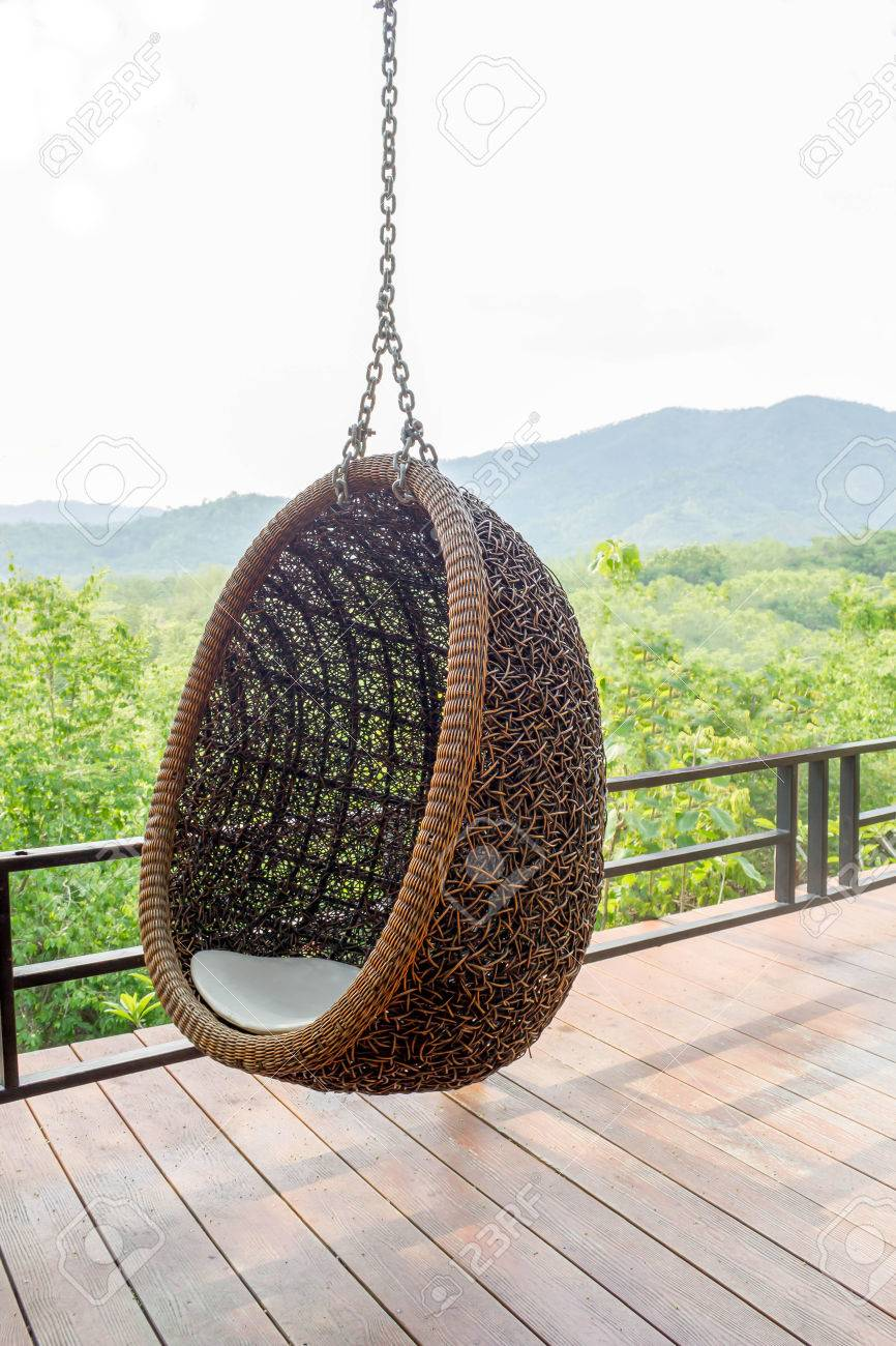 Merveilleux Rattan Lounge Hanging Chair With White Pillow At The Balcony With Green  Nature Background Stock Photo