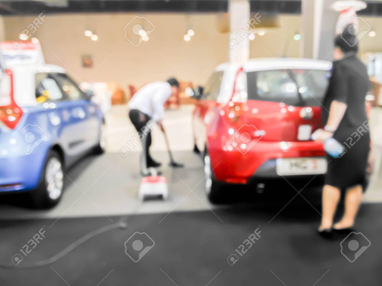 Salesman Clean Floor Of Car Showroom With Vacuum Cleaner Stock