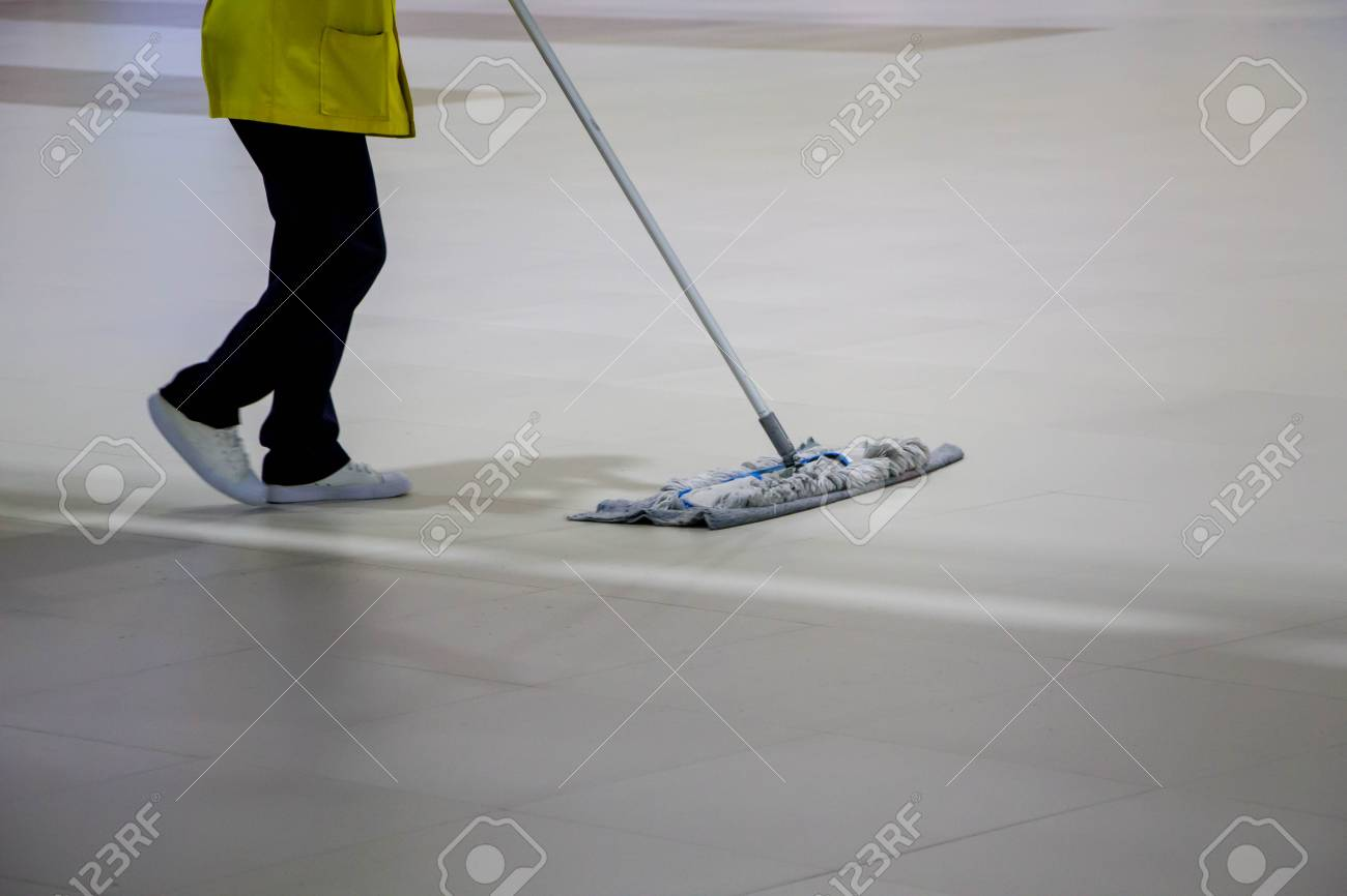Worker In Yellow Shirt Mopping Tile Floor In Office Stock Photo