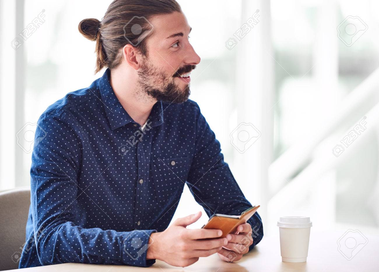 Jeune homme caucasien tendance aux cheveux longs attachés en chignon, à la  recherche hors caméra tout en maintenant un téléphone dans ses mains avec