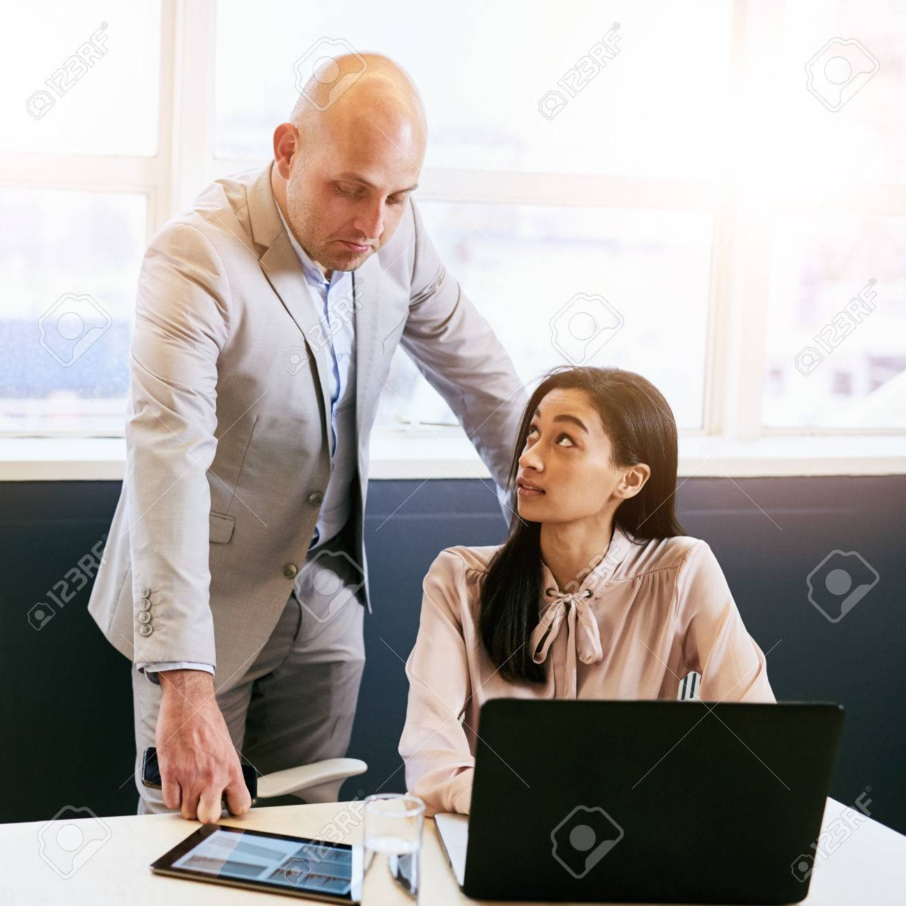 supervisor impressed the quality of work being done by his stock photo supervisor impressed the quality of work being done by his newly appointed female assistant who is working on a laptop and tablet while