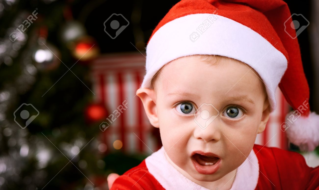 9a0949270e5a 9 month old baby boy with shocked expression looking into the camera  wearing a Santa Claus