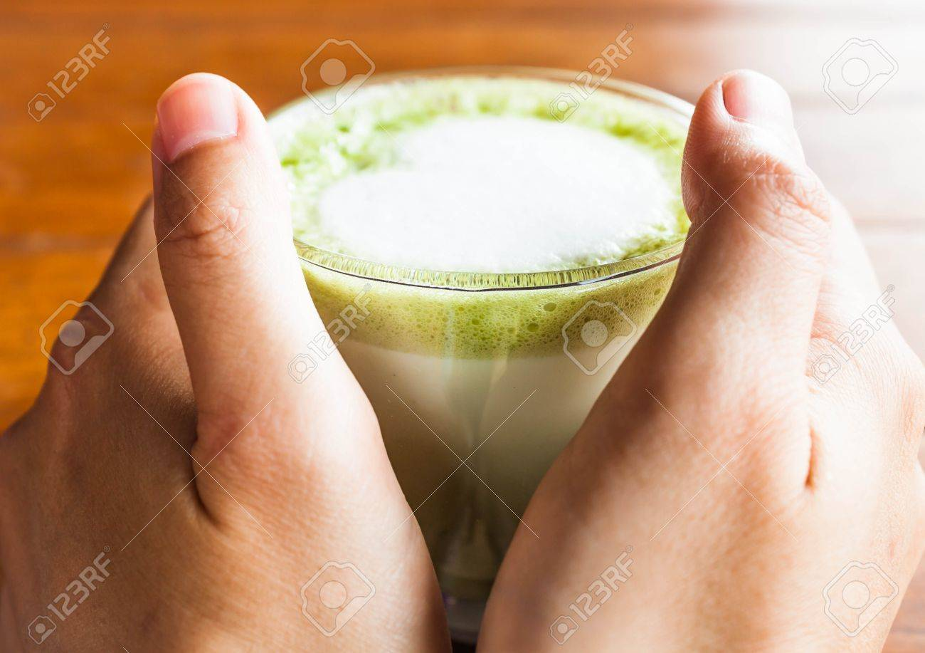 Hands hold hot drink of matcha green tea latte Standard-Bild - 20854250