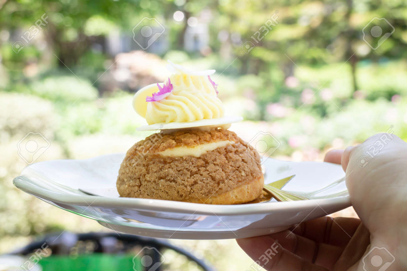Buns choux pastry sprinkled with white chocolate, stock photo - 168400221