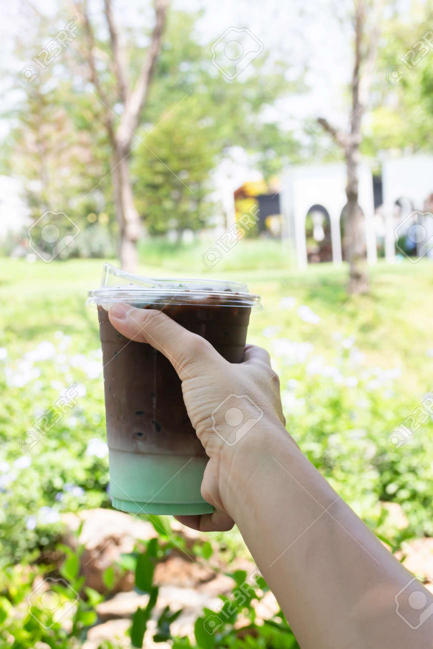 Female hand holding iced coffee drink in disposable take away cup, stock photo - 168400232