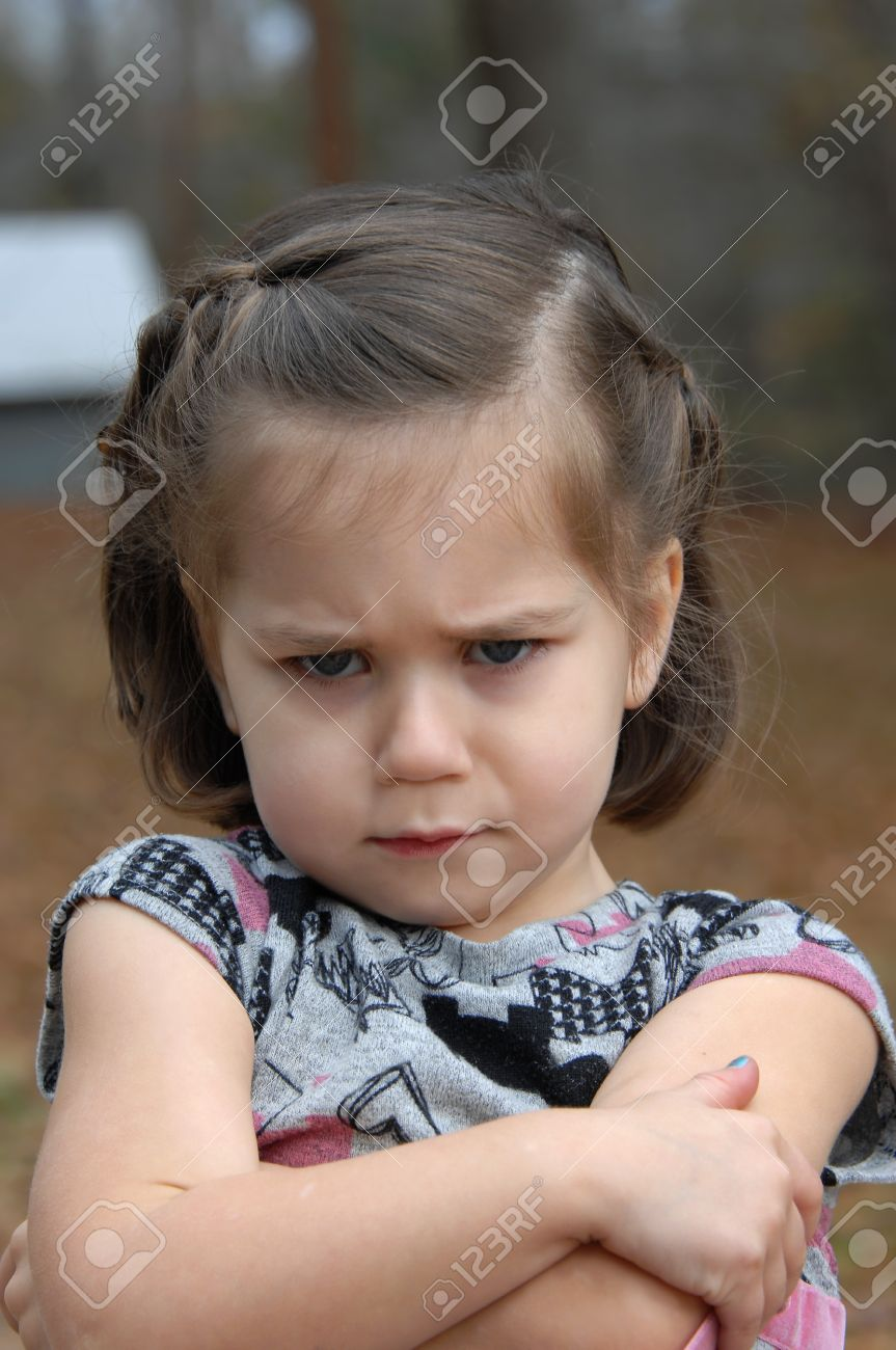 Arms crossed and eyebrows puckered, this little girl is upset and pouting She is standing outside - 14517420