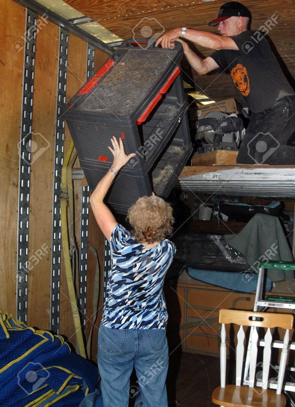 Couple work together to unload their moving van Husband is handing tool box to wife standing on floor It is hot work inside van - 14546549