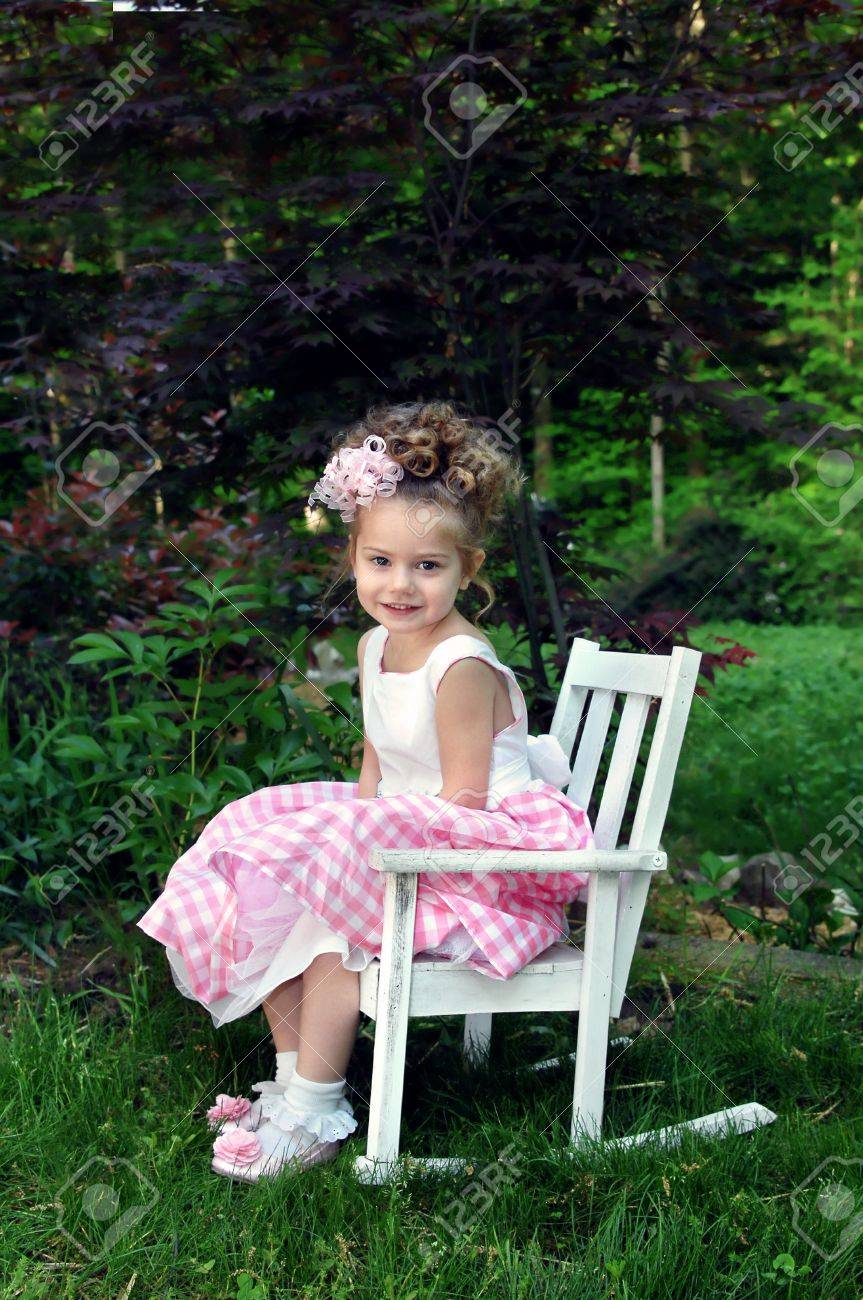 Little girl poses for picture on Easter Sunday morning.  She is wearing a pink and white gingham dress and curly ribbon hairbow.  She is sitting in a white wooden rocking shair and smiling. Stock Photo - 14517429