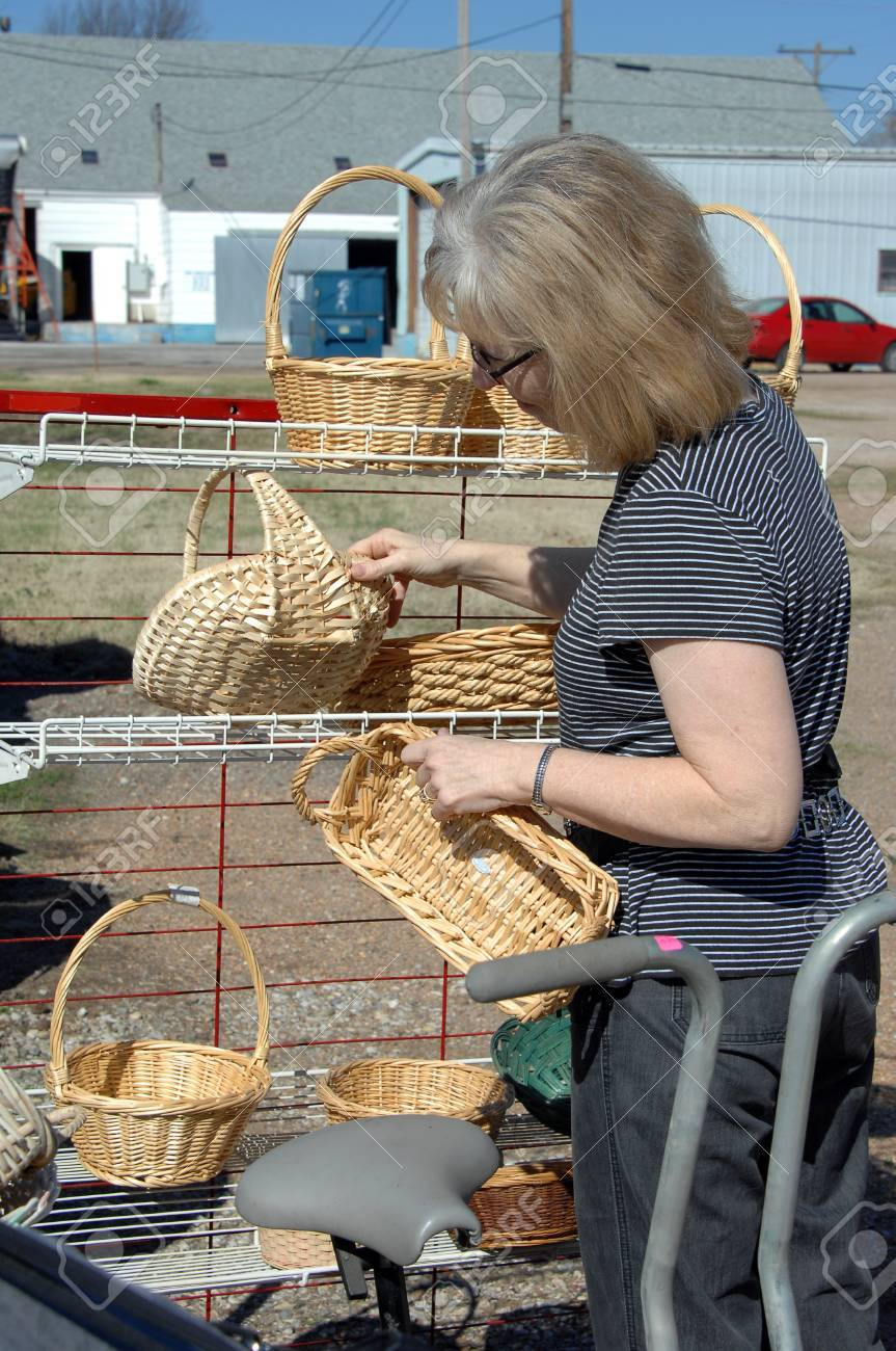 Garage saler, hunts through rack of wicker and ratan baskets for a bargain Stock Photo - 14824164