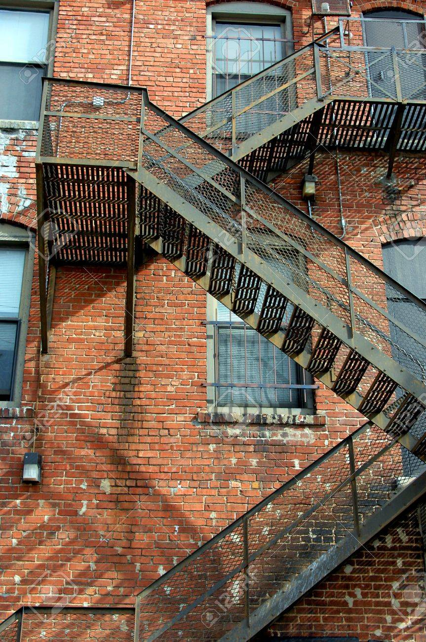 Fire Escape Winds Back And Forth Down The Side Of An Old Brick Apartment Complex In